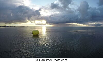 yellow buoy on early morning sea water near coastline and...