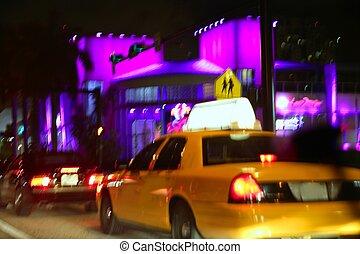 Yellow cab motion blur in Miami Beach  night city lights