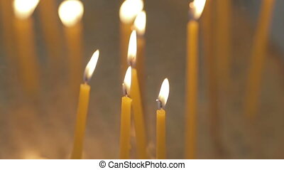Yellow candles burning brightly in the defocused background on a church.