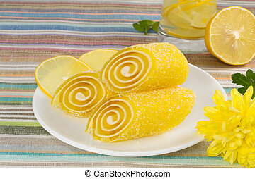 yellow candy fruit on a plate with lemon and flower