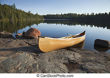 Yellow canoe on rocky shore of calm lake with pine trees