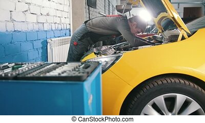 Yellow car in garage auto service - open hood - engine...