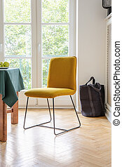 Yellow chair on a wooden floor with a balcony in the background in a dining room interior