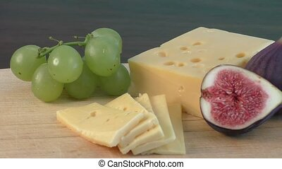 Yellow cheese and fresh figs on the wooden cutting board