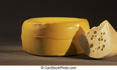 Yellow cheese wheel with wedge of Swiss cheese on an old...