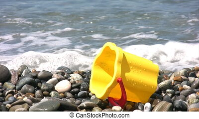 yellow children bucket on rocky beach, sea surf in...