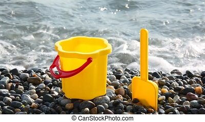 yellow children\'s bucket with scoop on stone seacoast