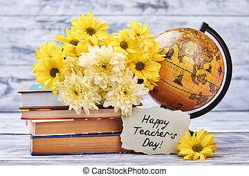 Yellow chrysanthemums, books and globe.