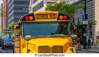 Yellow classic public school bus on the street, New York, Manhattan downtown.