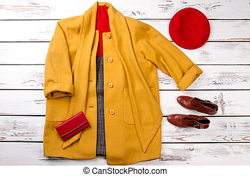 Yellow coat with pulled over sleeves.