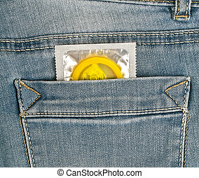 Yellow condom in blue jeans pocket