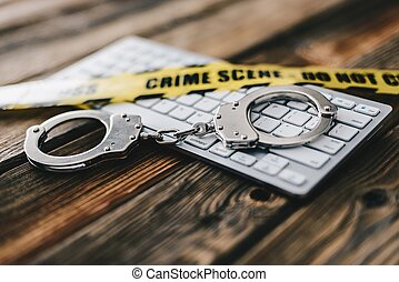 Yellow crime scene tape and handcuffs on computer keyboard.