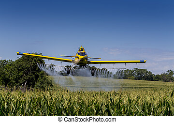 Yellow Crop Duster - A crop duster applies chemicals to a...