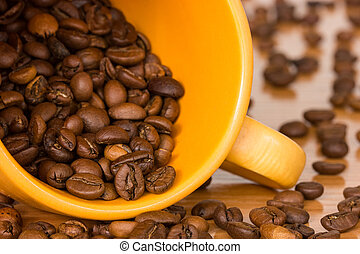 Yellow cup with many coffee beans