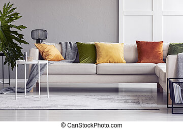Yellow cushions on white couch in modern living room interior with table and plant. Real photo