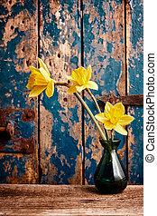 Yellow Daffodils in Vase in front of Wooden Door