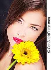 Yellow daisy on woman's shoulder