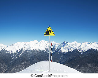 Yellow danger sign on ski slopes on the background of sky and winter mountains