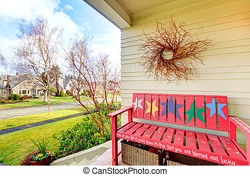 Yellow decorated porch with red bench, wicker baskets, dry branch, overlooking the front view