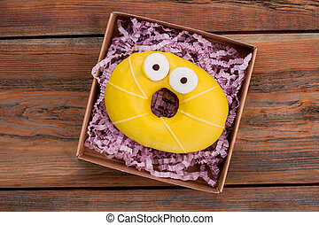 Yellow donut in box, top view.