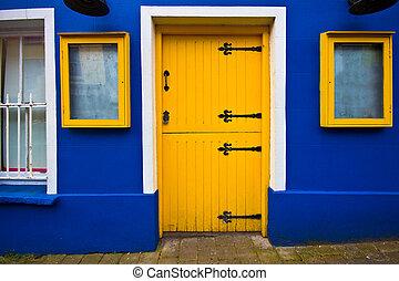 Bright yellow dutch door on blue facade