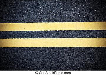 Yellow double dividing line over black highway asphalt closeup