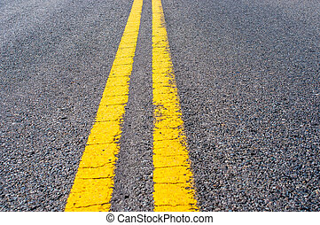 Yellow double dividing line over black highway asphalt
