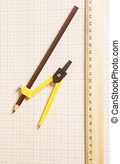 Yellow Drawing compass with black pencil and ruler on graph paper.Engineering concept.