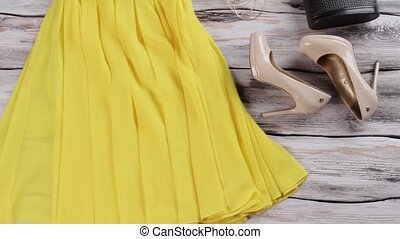 Yellow dress and heel shoes. Woman's yellow garment with...