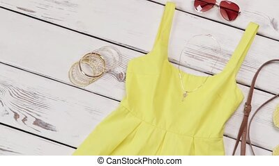 Yellow dress with light accessories. Casual yellow dress on shelf. Lady's aviator sunglasses with purse. High-quality clothing on sale.