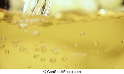 Yellow drink pour into a glass close-up slow motion