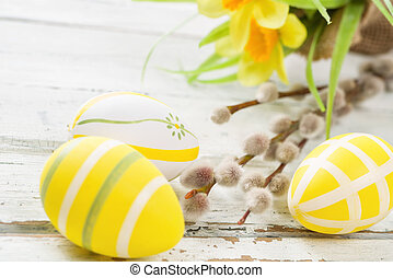 Yellow easter eggs on a rustic background with daffodils