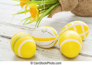 Yellow easter eggs on a wooden background with daffodils