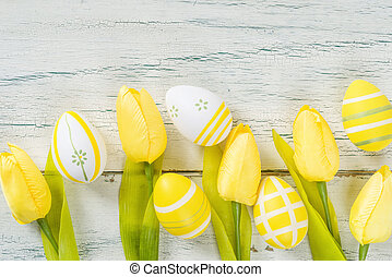 Yellow easter eggs with tulips on a white rustic background
