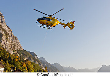 Yellow emergency helicopter in the Austrian Alps, Traunsee,...