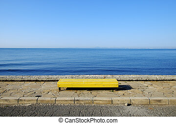 Yellow empty bench on blue sea background