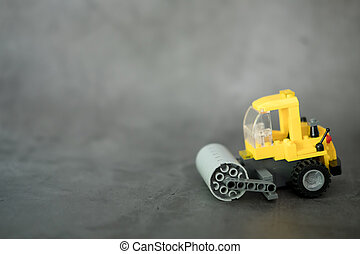 Yellow engineering motor vehicle with heavy roller toy