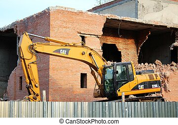 Yellow excavator and brick building - A photo of Yellow...