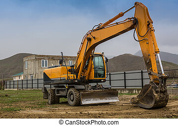 Yellow excavator at the construction of a cottage