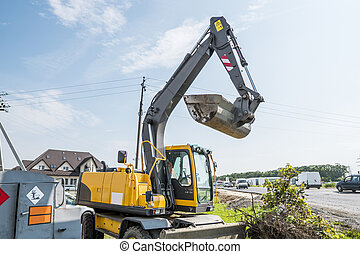 yellow excavator loader standing against sunny cloudy sky during road construction and repairing asphalt pavement works.