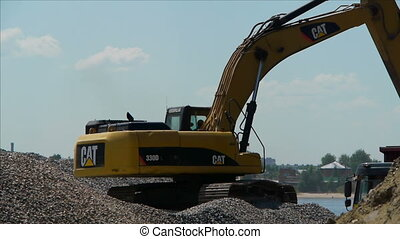Yellow excavator loading gravel