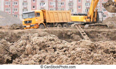 Yellow excavator loads clay using its big bucket in the...