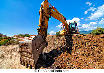 Yellow excavator moving soil and sand on road construction ...