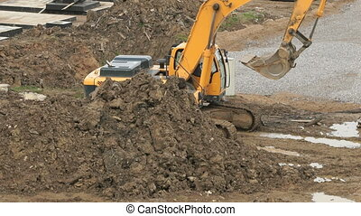 Yellow excavator on a construction site in summer - Large...
