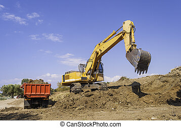 Yellow excavator on the construction site loads the soil into the body of a red dump truck