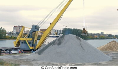 Yellow excavator pours a pile of rubble in front of a river. Its bucket suspended on cables.