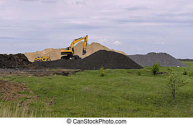 Yellow excavator working digging in sand quarry