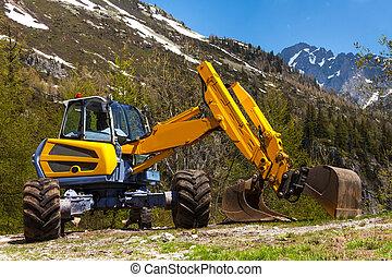 Yellow excavator working near mountains