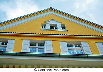 yellow facade of a city building - yellow facade and roof of...
