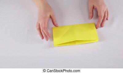 Yellow fish origami. White. Time lapse